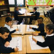 Students writing Chinese characters