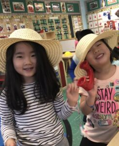 2 students wearing straw hats