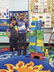 2 students standing next to blocks