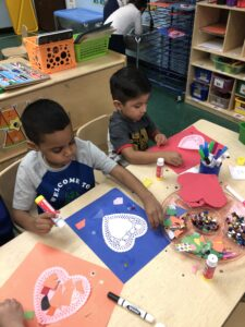 Students making valentines day crafts