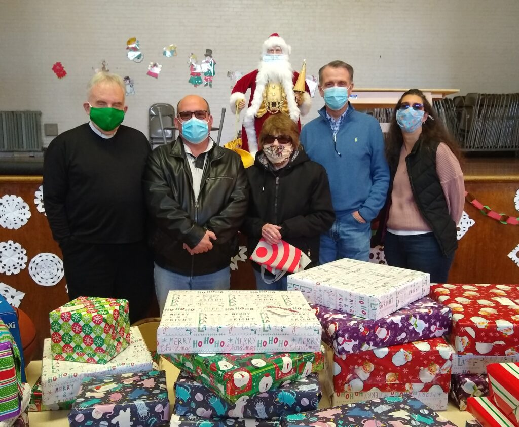 Monsignor John Vesey and members of Flushing Rotary Club stand behind table full of Christmas presents