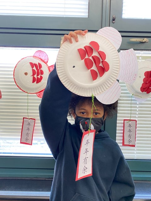 Grade 3 student holding paper plate art project