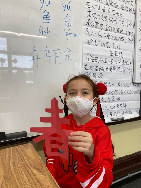 Student displaying Chinese character made from construction paper