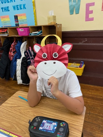 Grade 5 student at desk wearing ox mask